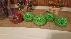 Very Hungry Caterpillar baby shower sweets table centerpiece. Dollar store votive holders with peanut M&M candies. Construction paper eyes and  pipe cleaner antennae.