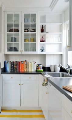 Kinda love this kitchen. White, glass cabinet doors, not-so-modern door and drawer pulls (as in warm, not nickel-cold), colorful bowls and mugs, books.