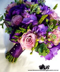 Like the soft pink roses in this arrangement and the deep purple ribbon on the handle