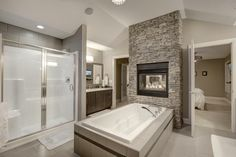 Double sided fireplace in ensuite. Double sided fireplace in master bedroom. Tub with fireplace, tile flooring, granite countertops and stained maple cabinets.