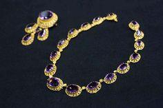 Este collar y broche, engastado con amatistas ovales y en forma de pera excepcionales, son parte de un conjunto de joyas que también incluye aretes y un peine.  Que data de alrededor de 1860, se encuentran entre las piezas más antiguas de la Colección Cartier.