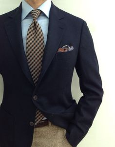 Navy sport coat, light blue shirt, plaid tie, beige tweed pants