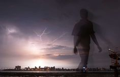 A man walks on the beach as  lightning lights up the night sky in Mumbai, India, Tuesday, Sept.28, 2... - AP