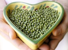 this is a dish of wasabi peas that is in a bowl that is in the shape of a heart. people in japan enjoy this as a nice snack.