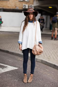 Gala Gonzalez in dark-blue denim, jeans shirt, oversized sweater, ankle booties, hat