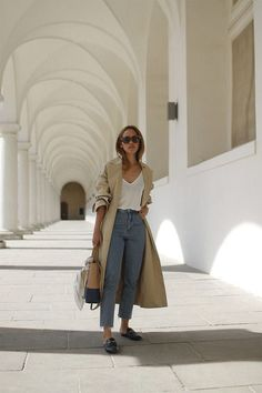 high-waisted cropped raw hem mom jeans + white t-shirt + light beige long maxi trench coat + black mule slides