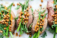 A recipe for vegan baked sweet potatoes topped with crispy roasted chickpeas, asparagus and fresh arugula.