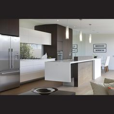 Mirrored walls enhance the light, airy feel of this contemporary kitchen in a new house. They also reflect the view and landscaping. In place of a traditional splashback, there is a window looking into a courtyard. The bench is flush with the window, which is glazed to reduce ultraviolet rays and heat.