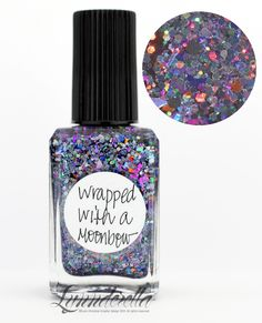 Lynnderella Limited Edition—Wrapped with a Moonbow contains assorted metallic and holographic shards mixed with dark grey holographic hexagons and microglitter in a clear base.