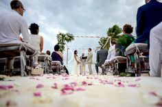 Tulum beach wedding ceremony with rose petals in the aisle. Photo: That Moment Photo