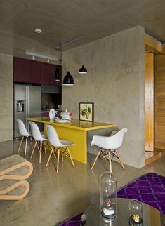 O acabamento todo em concreto dá um ar industrial a casa, que ganha vida com pontos coloridos, como a mesa amarela e o tapete roxo.