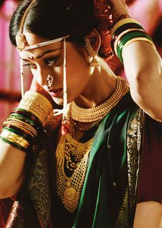 A Maharashtrian bride in traditional gold jewellery by Tanishq and pearl forehead accessory and ambi nath.