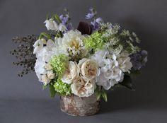 Artificial  silk flowers arrangement. White hydrangea,garden roses ,viburnum,sweet pea ,queen Anne's lace ,snow bell flowers in birch bark  vase.Design by Simone Vartan.