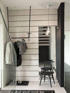 Sisääntuloaulan modernia ilmettä on rikottu vaakaan asennetuilla raaka-laudoilla. Sanna on kieputtanut mustaa lankaa vaaterekin päälle.