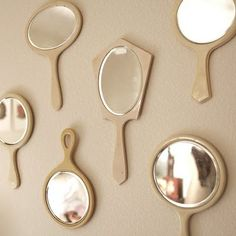 cute idea to hang a collection of vintage hand mirrors together.
