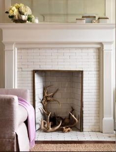 Antlers in the fireplace.  Love this idea instead of the (getting old) idea of filling your fireplace entirely with birch logs.