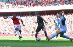 Theo Walcott tucks in the opening goal of the game between Arsenal and Stoke - The Emirates Stadium enjoying the game and the sunshine