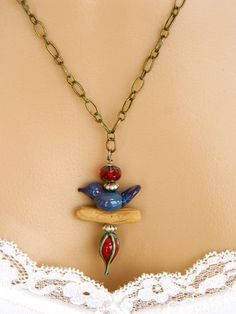 This charming costume jewelry necklace is perfect for bird lovers! A beautiful red lampwork bead with green overlay was artisan made by Nikki Thornburg along with the cute little dark blue bird. This bird necklace is a delight to the eyes. The bird sits on a polymer clay branch that I made and is topped with a dark red Czech glass bead. The pendant in this Etsy beaded necklace is connected to antique brass chain. This blue necklace for women is 22 inches long and has a 3 inch extension…