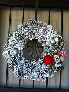 70 DIY Wreaths! I want to do this one for Christmas. White pine cones with a big red ribbon on the bottom center instead of the decorations to the side of this one.