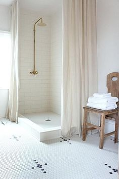 Exquisite white bathroom features a corner white subway tiled walk in shower boasting a vintage brass exposed plumbing shower kit and covered in two ivory linen shower curtains.