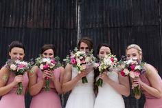 2 brides and bridesmaids peeking behind flowers
