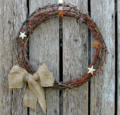 Barb wire wreath with burlap bow, and red berries and rusty stars on Etsy, $25.00