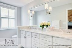 White and gray master bath with gray walls framing white double vanity and marble countertops with his and her sinks.