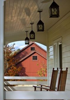 This traditional white paneled patio was designed by John B. Murray Architect of New York City.  A red painted barn is seen in the distance.