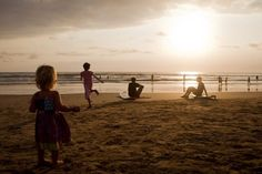 Children playing and surfers watching the sunset on Kuta Beach. - Natalie Grono/Getty Images