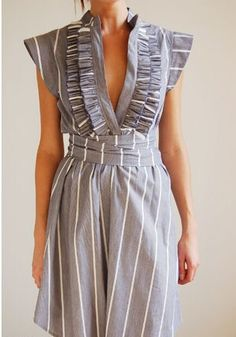Feminine. Like the wrap, the ruffles, the waist (not so sure about the fabric, the colour and print).