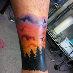 Man With Sunset Forest And Colorful Sunset Tattoo On Ankle
