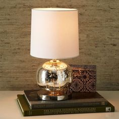 "Mini Abacus Table Lamp - Mercury | West ElmGlass act. The Mini Abacus Table Lamp's shapely glass sphere is a glamorous statement piece on desks or consoles.   6.5""diam. x 14.9""h. Mercury glass; iron base with plated antique bronze finish. White linen shade."