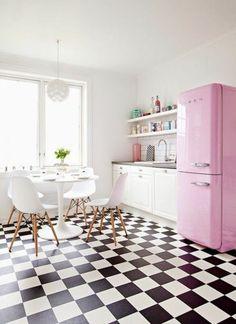 Une cuisine avec un carrelage damier en noir et blanc et un réfrigérateur rose rétro