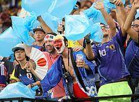 青いゴミ袋を振りながら応援するサポーターたち=西畑志朗撮影