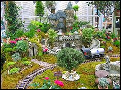 Awesome Fairy Garden! Little boys would love the trains that wind round the railroad tracks.