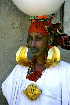 Fulani woman wearing traditional pure gold earrings and necklace pendant. Scattered through many parts of West Africa, the Fulani are the largest nomadic group in the world. We Are The World, People Around The World, We The People, Out Of Africa, West Africa, African Jewelry, Tribal Jewelry, Folklore, Mouth Tattoo