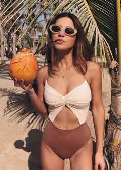 Don't know what to do with your hands? Grab a coconut, a sun hat, a beach bag—anything.