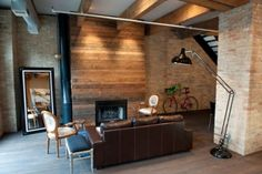 Eclectic living room with brick walls and wood around the fireplace