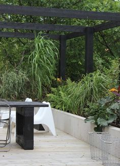 Black pergola could be over large concrete pavers and raised garden bed surrounding