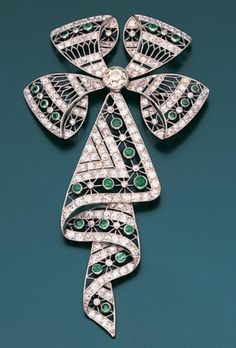 An emerald and diamond brooch Of ribbon-bow design, the central old brilliant-cut diamond radiating four finely pierced loops of millegrain-set old brilliant and single-cut diamonds and circular-cut emeralds, suspending a similarly set pendant designed as folds of ribbon.