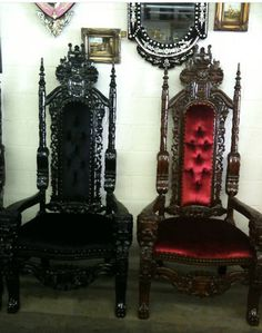 Two very ornate throne-like armchairs. One is black lacquered wood with black padding, the other brown lacquered wood with red padding.