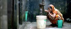 A woman drinking from cupped hands at a water pump.