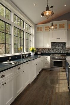 Gorgeous transitional kitchen. Nautical style pendant white cabinetry and vaulted ceiling