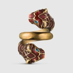 Gucci tiger head ring in metal with an aged gold finish and red enamel. The tiger eyes are blue Swarovski crystals.