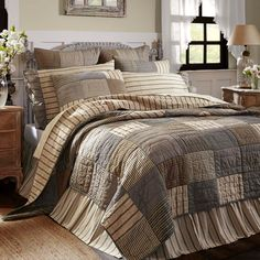 The Sawyer Mill bedding collection features a simple block pattern in various plaid and stripes that work perfectly to set a Farmhouse mood for the bedroom. This cozy quilt is ash grey, creme, and black, 100% cotton machine pieced and echo hand-quilted for years of enjoyment. Reverses to dark creme and charcoal grain sack stripes.