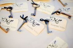 Vintage keys tied with black ribbon to elegant thank you cards for a traditional wedding.