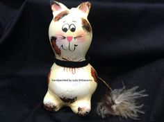 This calico kitty is hand painted and has a yarn twine tall with a big fluffy end. He also has a suede collar. He would make a great gift