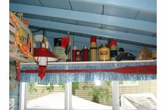 Porch shelf with vintage thermos bottles.