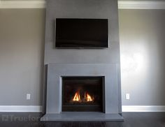 This is a contemporary gas fireplace surround cast in concrete. by Trueform concrete Fireplace Tv Wall, Concrete Fireplace, Bedroom Fireplace, Fireplace Remodel, Modern Fireplace, Living Room With Fireplace, Fireplace Surrounds, Fireplace Mantels, Corner Fireplaces