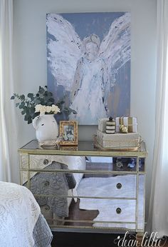 This angel painting nicely accents this mirrored chest in our master bedroom. A gold tray from HomeGoods helps keep items contained and makes a nice little vignette. (sponsored pin)